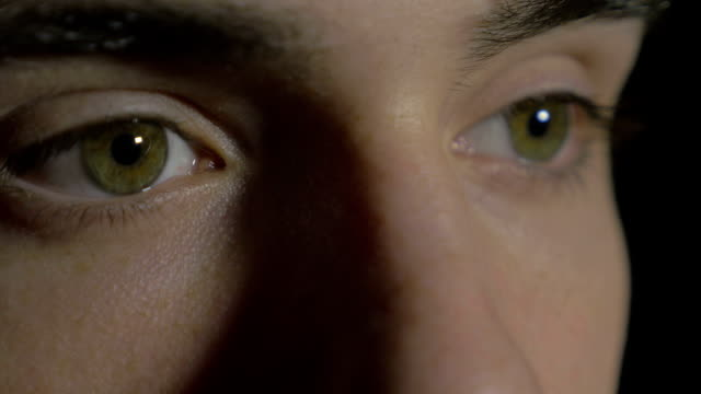 Close-up of a young man eyes in the dark video