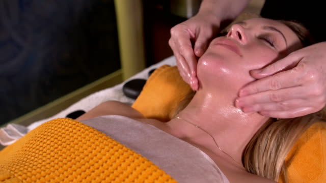 Close-up of a young woman getting spa treatment at beauty salon. spa face massage. facial beauty treatment. spa salon. video