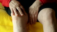 Close-up of an Old Woman Massaging Her Knee on the Couch video