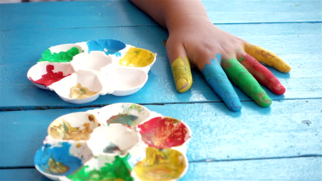 Close-up of Asia children hand on table with colorful finger, slow motion shot. video