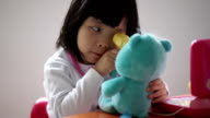 Closeup of Asian chinese toddler playing pretend doctor with her teddy bear video