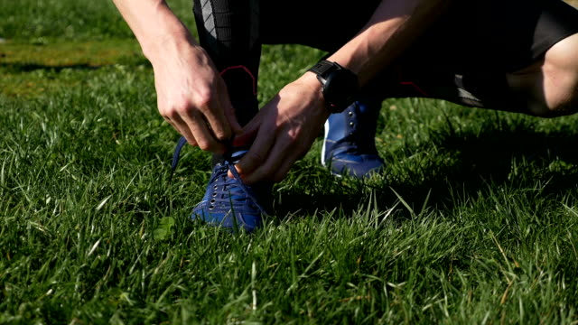 Closeup of athlete man tying shoelaces before jogging in the park video