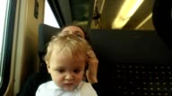 Closeup of baby traveling by train. Mother talking on cellphone with baby on her laptop. Mother and baby on train video