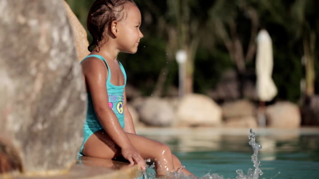 Close-up of baby's feet splashing the water in the swimming pool video
