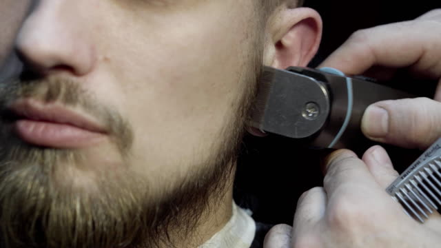 Closeup of barber cutting beard with a trimmer at a barber shop video