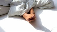 closeup of bare feet of woman in white bed on a sunny morning video