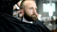Close-up of beautiful attractive adult man with beard in a barber shop video