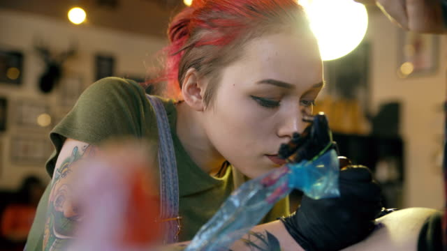 Closeup of beautiful young red haired girl tattoo artist tattooing picture on leg of her girl client in studio indoors video