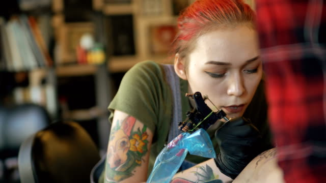 Closeup of beautiful young red haired woman tattoo artist tattooing picture on leg of her girl client in studio indoors video