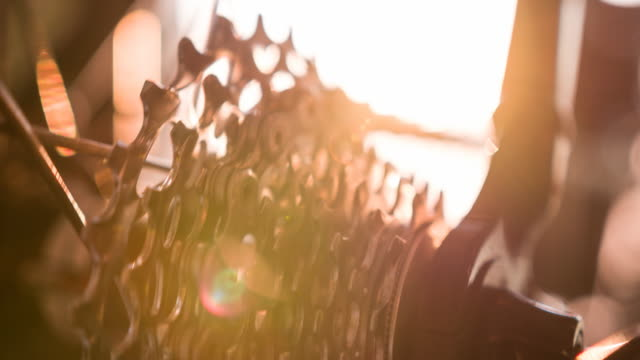 Close-up of bicycle derailleur gears in motion at sunrise video