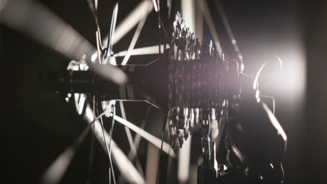Close-up of bicycle gear and chain on black background, illuminated by artificial light video