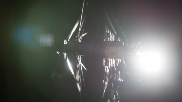 Close-up of bike tyre and gears at night, illuminated by artificial lighting video