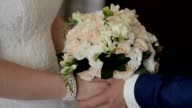 closeup of bride and groom exchanging wedding rings over green nature background video