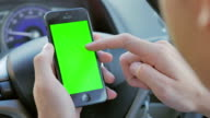 Close-up of businessman using smartphone in car,Green screen video