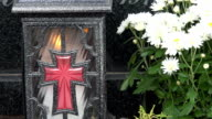 Closeup of candle box with cross and white chrysanthemum flowers on grave. video