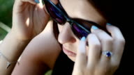 close-up of Caucasian girl wears sunglasses in slow motion video