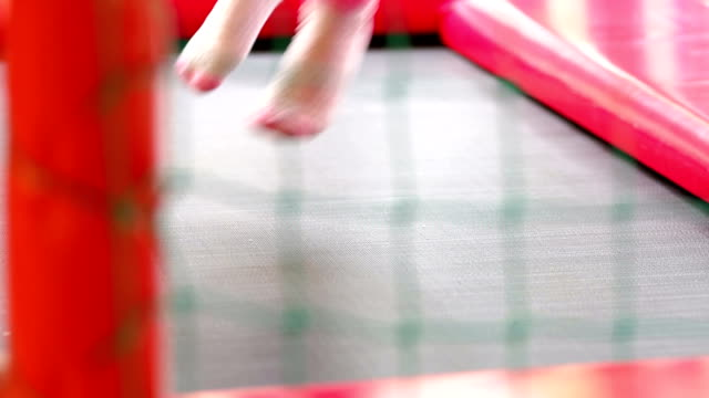 Close-up of child's feet on the trampoline, slowmo video