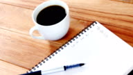 Close-up of coffee cup with diary and pen video