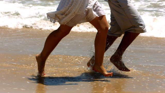 Closeup of couple's feet running in ocean surf video