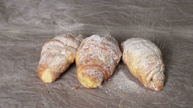 Close-up of croissants sprinkled with icing sugar. video