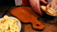 Close-up of cutting banana on wooden board with knife video