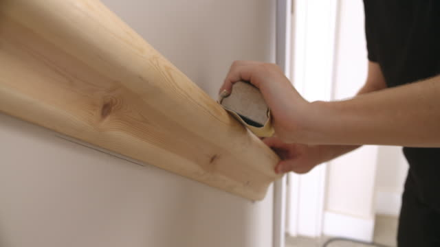 Close-up of decorator's hands sanding a wooden handrail video
