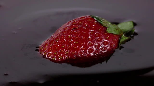 Close-up of delicious strawberry falling into chocolate syrup video