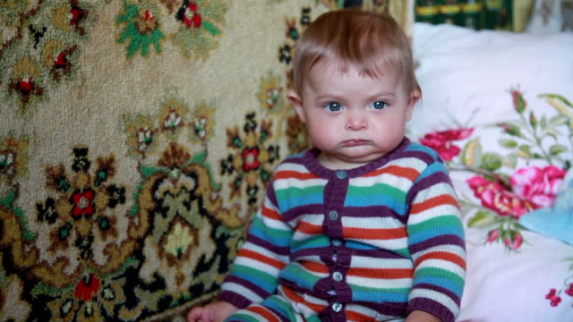 Close-up of displeased baby looking at camera video