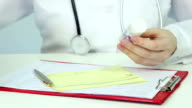 Closeup of doctor's hands writing prescription, assigning patient's medication video