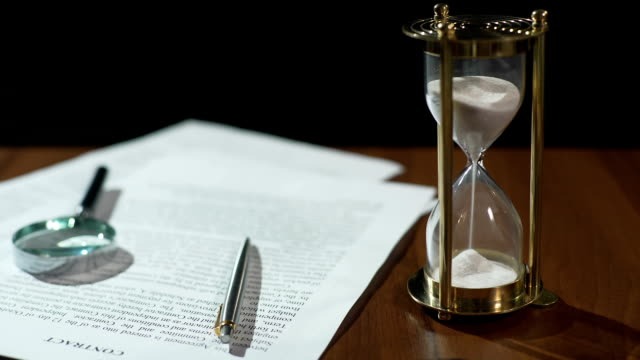 Close-up of document and hourglass on table, contract validity period expiring video