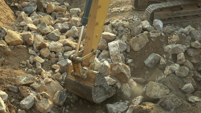 Close-up of excavator bucket loading rocks, stones, earth and concrete bricks from demolition site. video