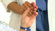 Close-up of Female African doctor holding her Caucasian patient's hand video