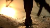 Close-up of female feet walking barefoot on sandy lake shore at sunset video