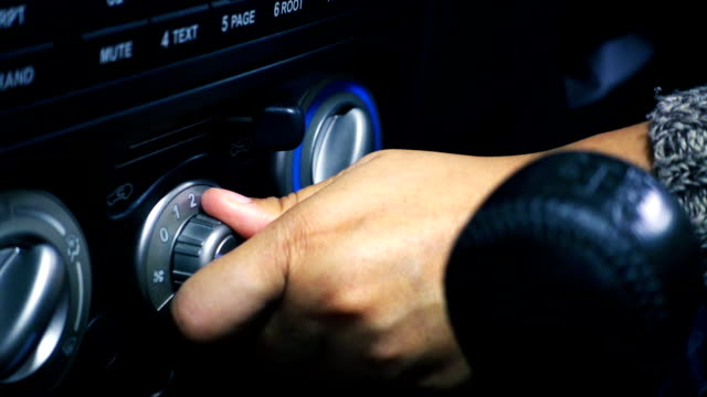 Close-up of female hand adjusting button control air conditioning on a vehicle's dashboard. Slowmotion shot video