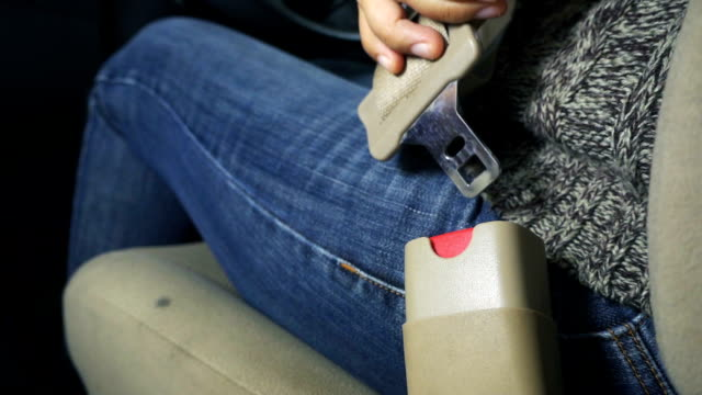 Close-up of female hand fastening car safety seat belt. Concept driving car. Slowmotion shot. video