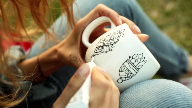 Close-up of female hands drawing a pattern on a white cup. Girl paints ornament sitting on the grass in the evening. video