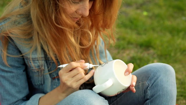 Close-up of female hands drawing a pattern with paint from a tube on a white mug. Smiling girl paints ornament sitting on the grass in the evening. video
