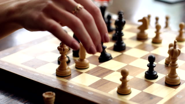Close-up of female's hand with ring playing chess. video