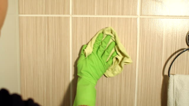 Close-up of girl in gloves cleans a tile surface. video
