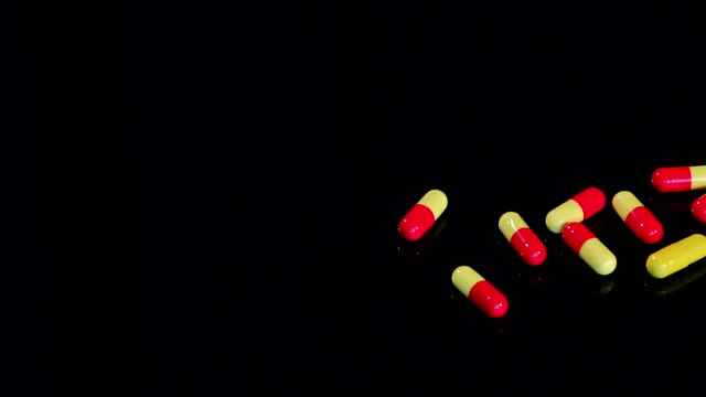Close-up of handful of pills on black background. video