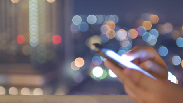 Close-up of Hands Touching smartphone on the rooftop with circle bokeh light of city at night time video