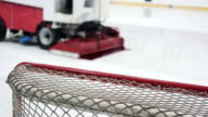 Close-up of hockey net, ice resurfacer driving rink to make surface smooth video