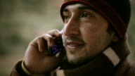 Close-up of Indian young man talking on phone in winter video