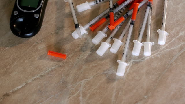 Closeup of insulin syringes,glucometer and insulin video