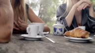 Close-up of italian breakfast with people. focus on croissant brioche, cup of coffee and cup of cappuccino in natural rural scenic outdoor during summer sunny day morning in tuscany - slow-motion HD video footage video