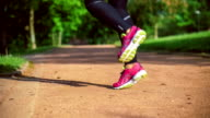 Close-up of jumping feet on the jump rope. Outdoor sports. Girl jumping on a skipping rope in park path with a green grass on background. video