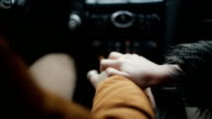Close-up of lovers hands. Man and woman sitting in a car. People support each other, express love video