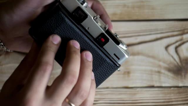 Closeup of male hands set new film. vintage camera. rangefinder camera video