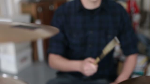 Closeup of man playing drums in garage band video