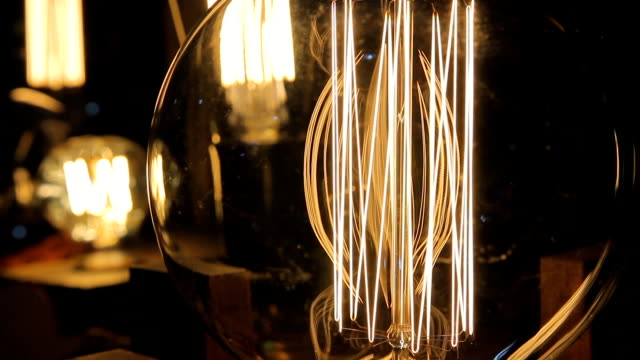 Closeup of metal wire inside illuminated Edison light bulb, vintage objects video